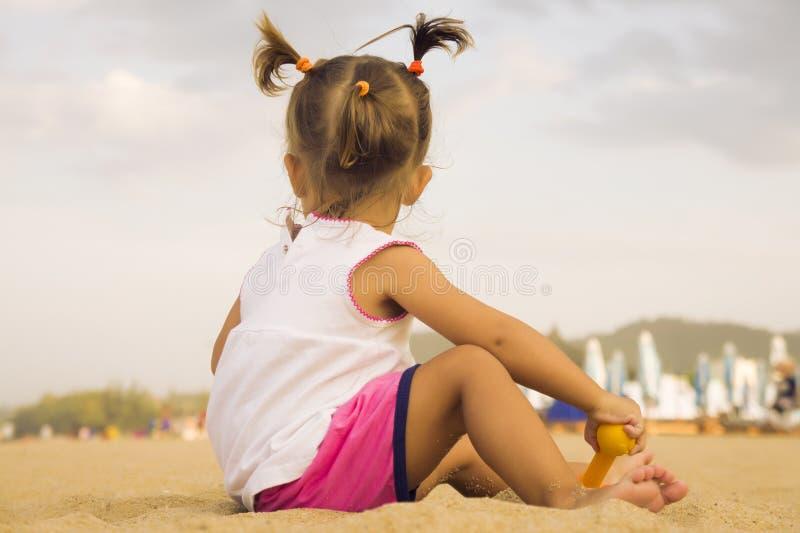 坐与他的回到照相机和使用与在沙子的玩具犁耙的美丽的婴孩在海滩 免版税库存图片
