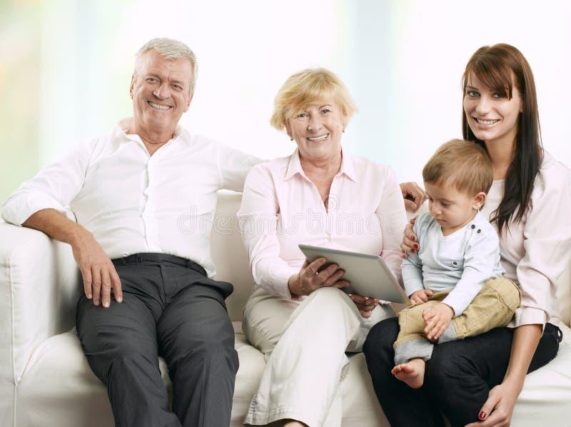 坐与他们的女儿和孙子的资深夫妇 免版税库存图片
