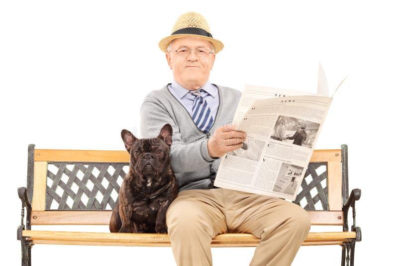 坐与他的狗和读报纸的资深绅士 免版税库存照片