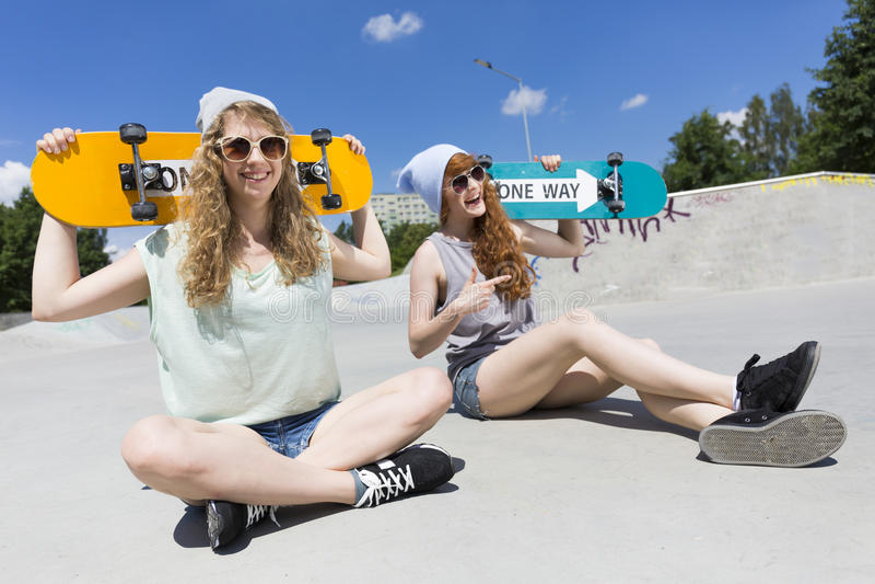 坐与他们的滑板的女孩 免版税库存图片