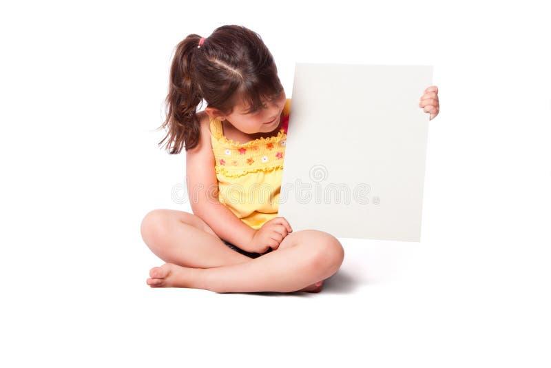 坐与whiteboard的逗人喜爱的女孩 库存图片