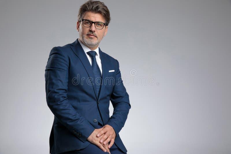 坐严肃的看的businessmn,当穿着典雅的蓝色衣服时 免版税库存照片