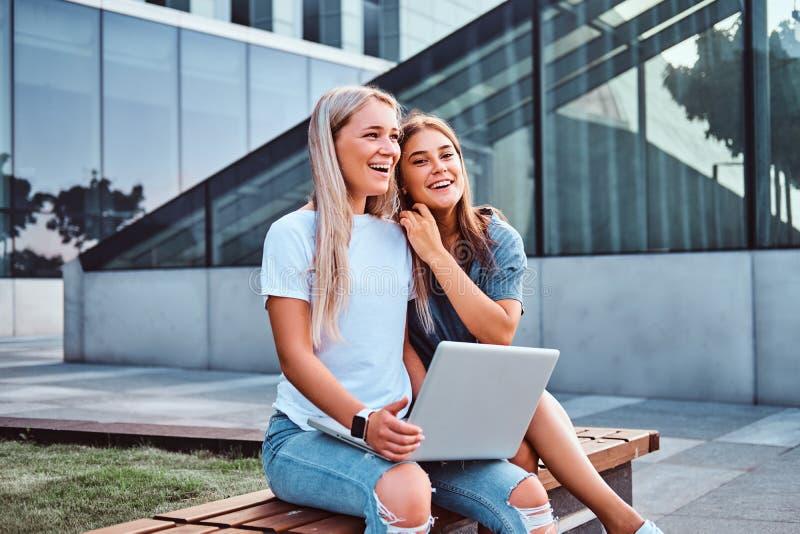 坐举行膝上型计算机和看照相机的两个美丽的女孩,当坐在背景的长凳时 免版税库存图片