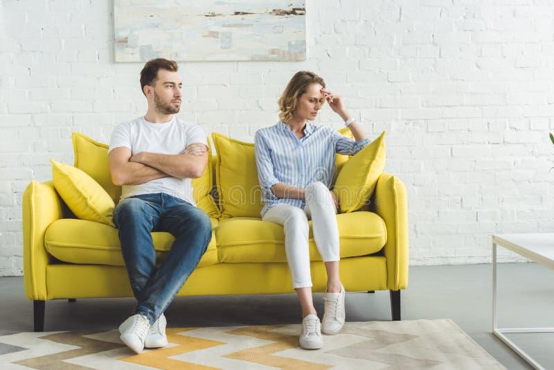 坐以后的生气夫妇在墙壁前面的长沙发争论 图库摄影