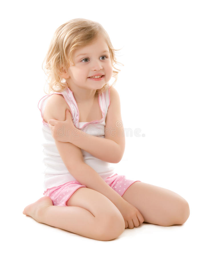 坐佩带的白色的女孩小的睡衣 库存照片