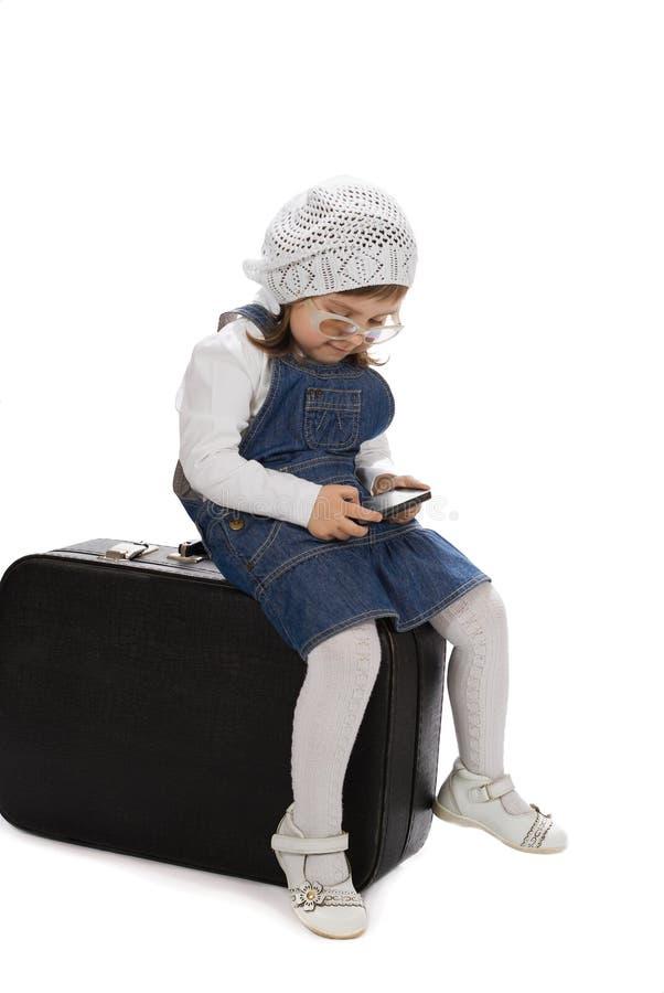 坐使用与电话的手提箱女孩 库存图片