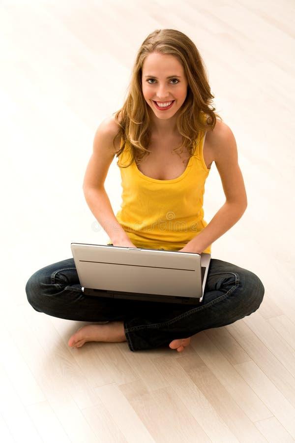 坐使用妇女的楼层膝上型计算机 库存照片