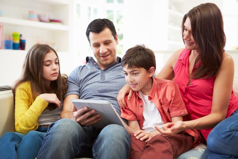 坐使用数字式片剂的西班牙家庭 免版税图库摄影