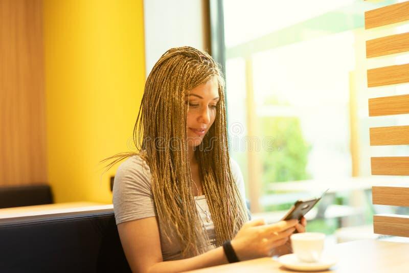 坐使用机动性的年轻女人在自助食堂 免版税库存图片