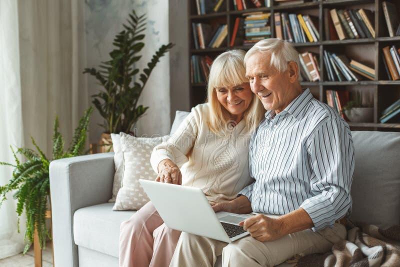 坐使用膝上型计算机的资深在家一起夫妇退休概念指向屏幕 免版税库存照片