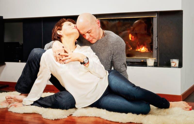 坐充满激情的美好的对在毛皮地毯在firep附近 免版税库存照片
