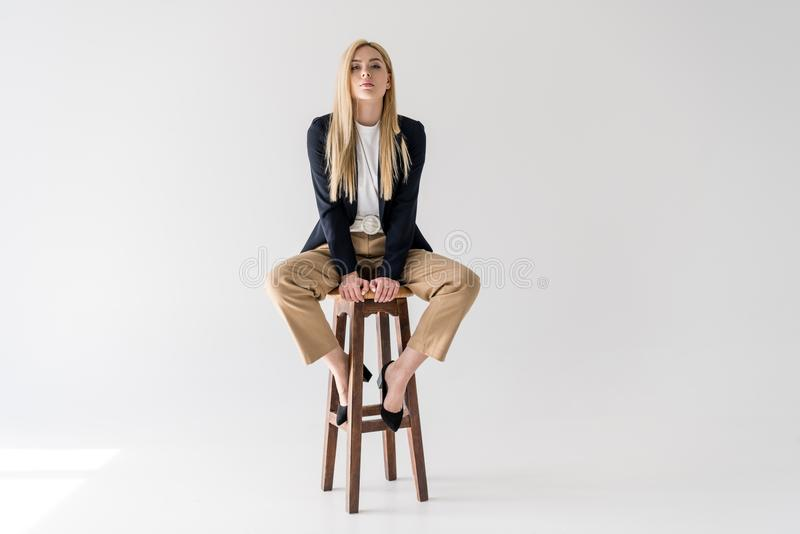 坐凳子和看照相机的时髦的衣裳的美丽的年轻白肤金发的妇女 免版税库存照片
