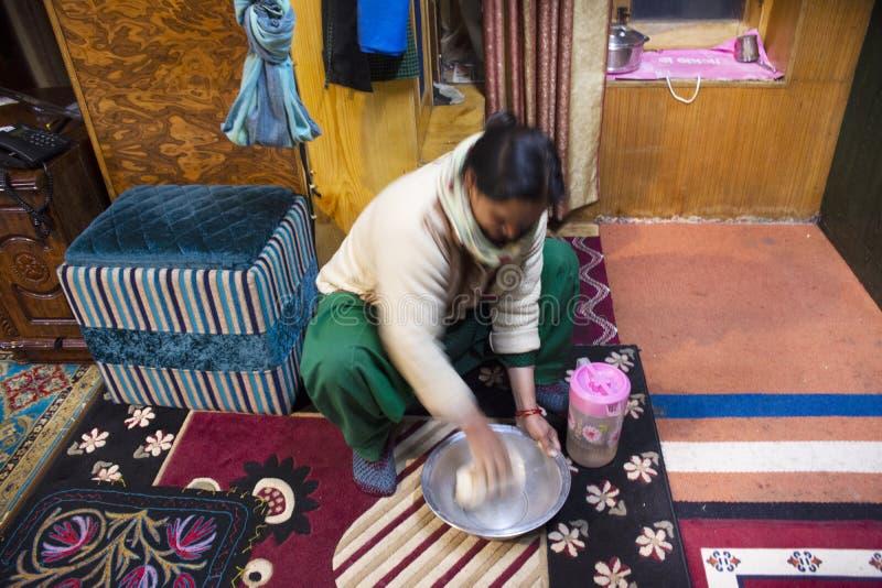 坐印度妇女的人民打谷烹调晚餐的面粉食物在客舍里厨房屋子在莱赫拉达克村庄在印度 免版税库存照片