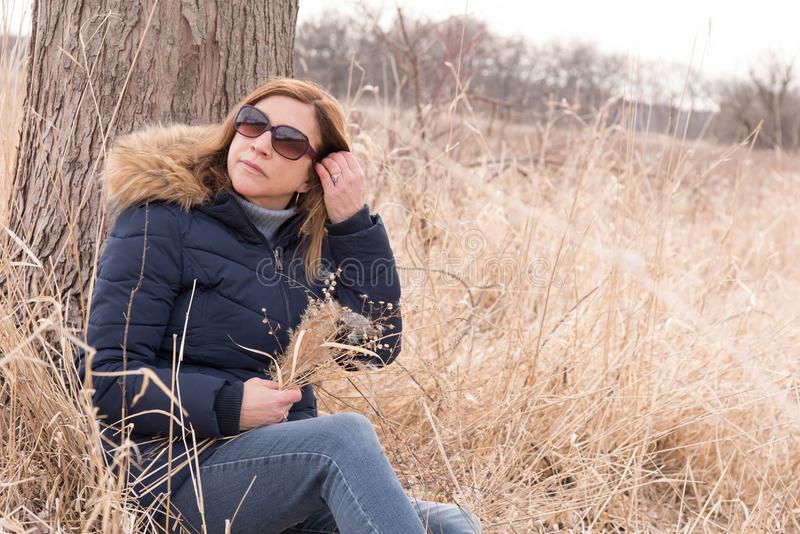坐反对在举行新鲜的被采摘的wildflo的领域的树的妇女 库存照片
