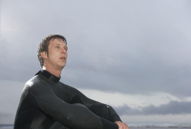 坐反对多云天空的体贴的男性冲浪者在海滩 免版税库存照片