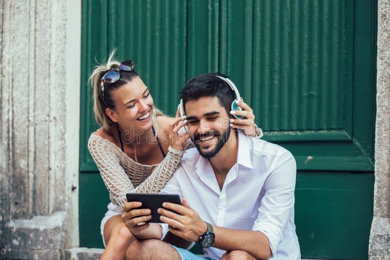 坐台阶使用片剂和听到音乐的年轻旅游夫妇 免版税库存图片