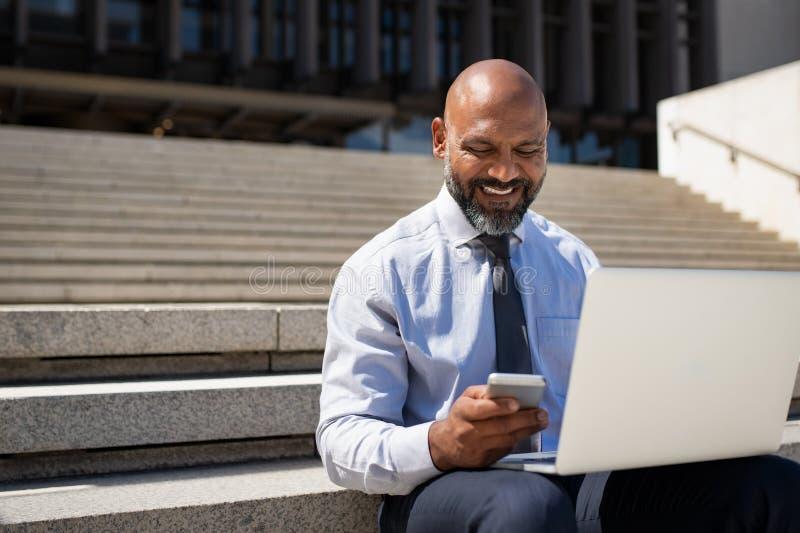 坐台阶和研究膝上型计算机的商人 免版税库存图片