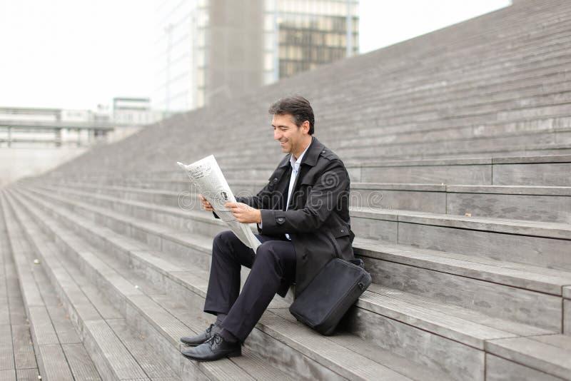 坐台阶和读报纸的男性企业家庭教师 免版税库存照片