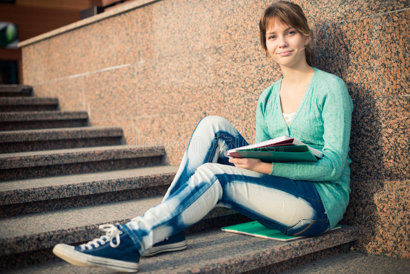坐台阶和读笔记的女孩 库存照片