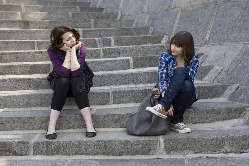 坐台阶青少年二的女孩都市 免版税库存照片