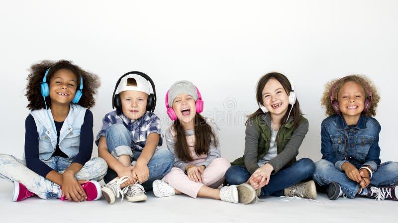 坐听到音乐的逗人喜爱的小孩 免版税图库摄影