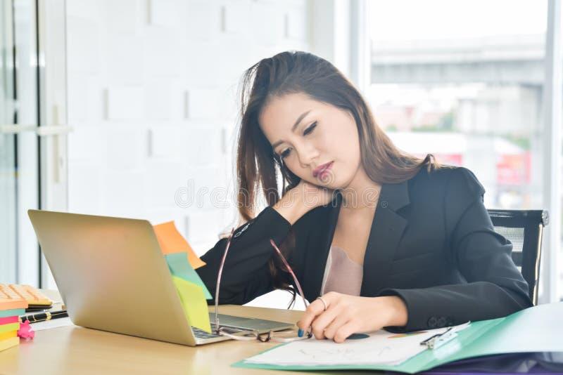 坐和举行脖子由于痛苦肩膀和脖子痛的被注重的女商人在现代办公室,办公室 免版税库存图片