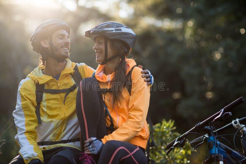 坐和互动互相的骑自行车的人夫妇 免版税库存照片
