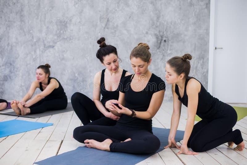 坐和交往与小组的逗人喜爱的女孩在他们的瑜伽类以后 免版税库存照片