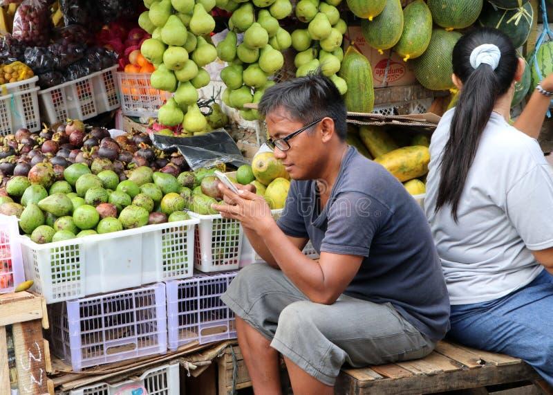 坐和使用在果子商店前面的印度尼西亚人手机在新鲜市场上在雅加达 库存照片