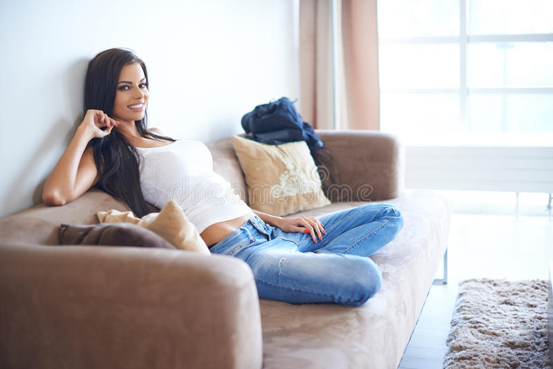 坐和倾斜对长沙发的微笑的妇女 免版税库存照片