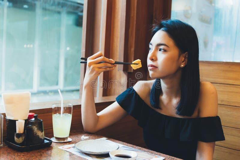 坐和吃单独日本食物的可爱的亚裔妇女在餐馆 免版税库存照片