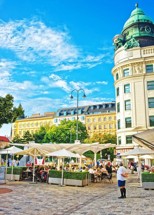 坐和吃在咖啡馆莫扎特街道大阳台的人们  库存图片