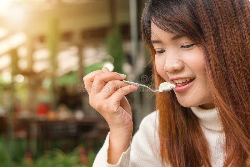 坐和吃点心的可爱的愉快的逗人喜爱的年轻亚裔妇女在户外咖啡馆 食物,垃圾食品,烹饪,烘烤和假日 免版税库存照片