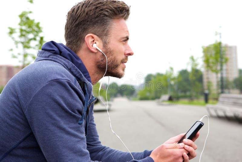 坐和听到音乐的中年活跃男性 免版税库存图片