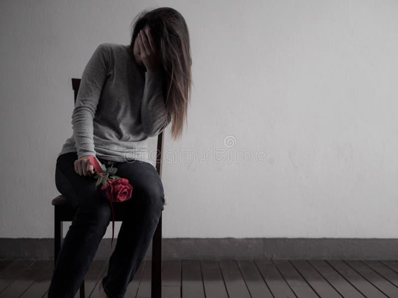 坐和哭泣与红色玫瑰的沮丧的打破的有之心的妇女 免版税库存图片