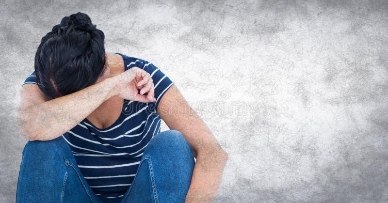 坐和哭泣入胳膊的妇女对有难看的东西覆盖物的白色墙壁 免版税库存图片