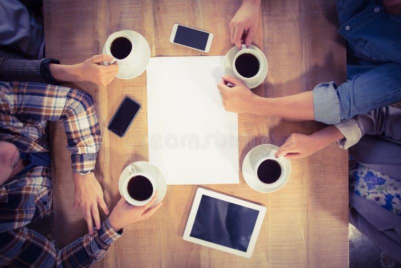坐和喝咖啡的朋友 免版税库存照片