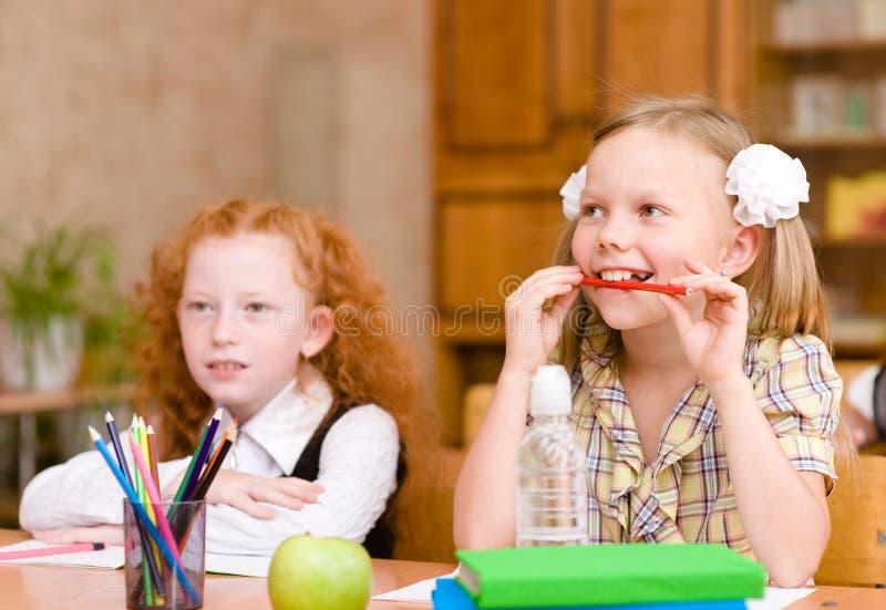 坐和学习在学校课程的小女孩 免版税库存图片