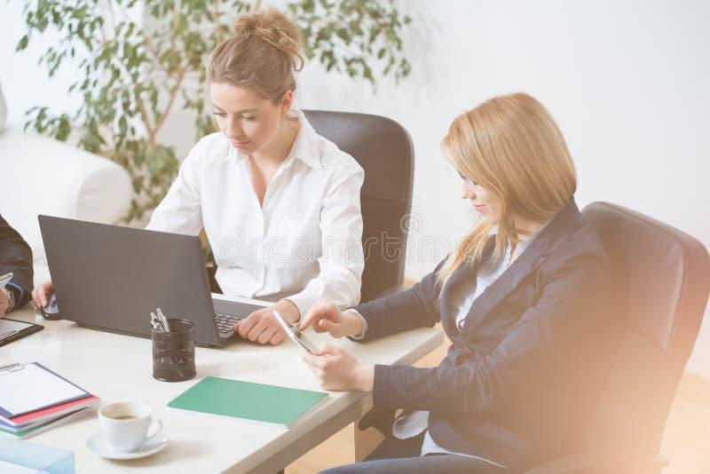 坐和工作在办公室的妇女 免版税库存图片