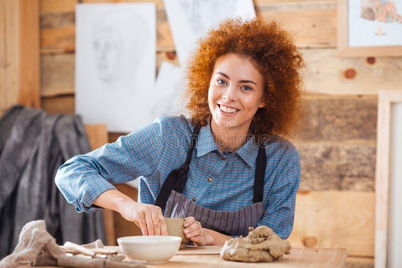 坐和工作在艺术瓦器演播室的快乐的妇女陶瓷工 库存图片