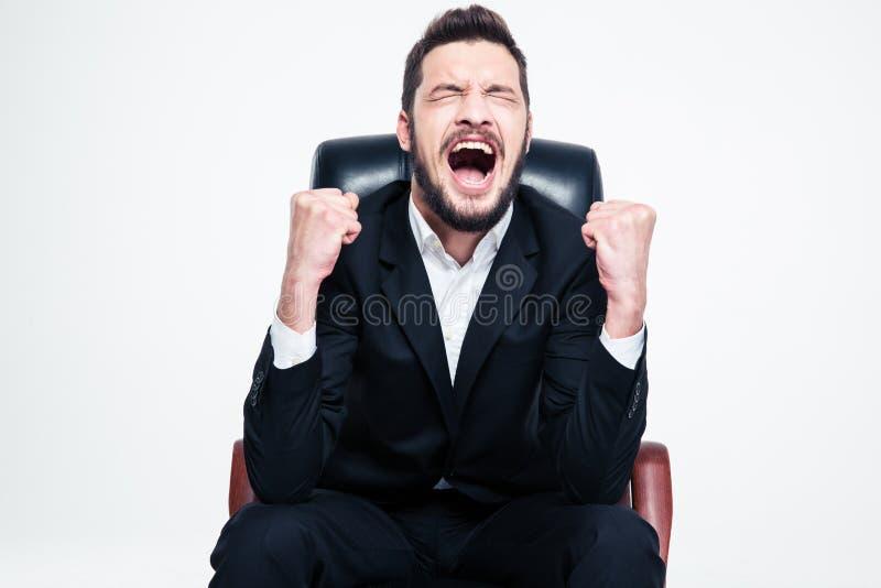 坐和庆祝成功的高兴愉快的有胡子的年轻商人 免版税库存图片