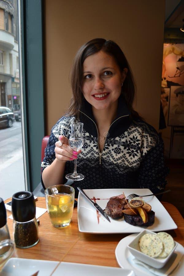 坐和微笑在一个咖啡馆的妇女用食物和酒精 库存照片