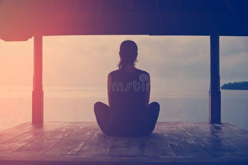 坐和思考在海洋附近的妇女剪影在日出 库存图片