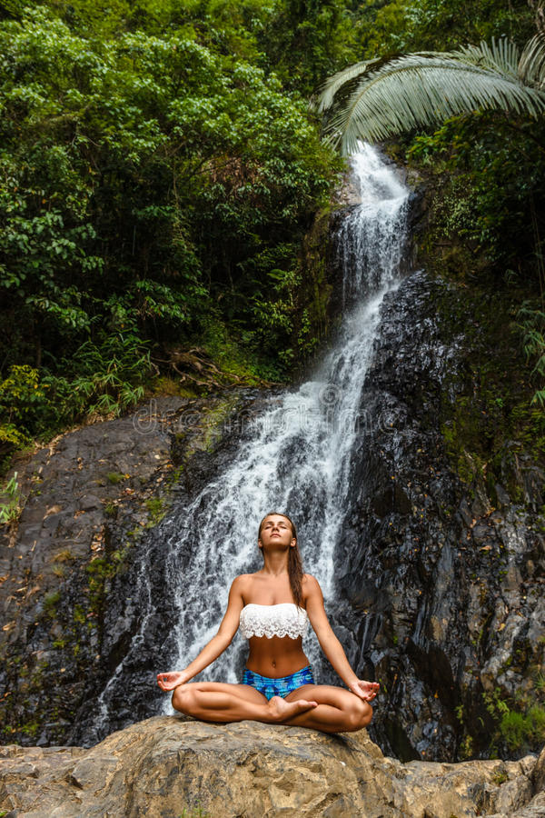 坐和思考在自然瀑布的女孩 库存照片