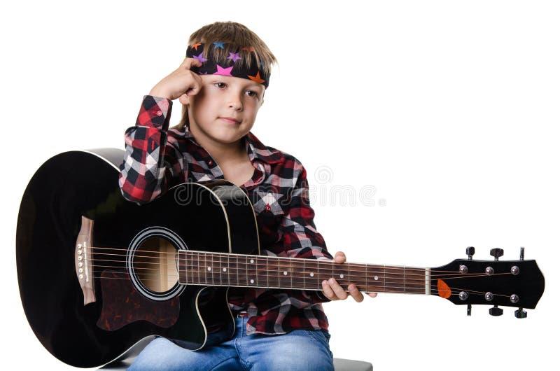 坐和拿着吉他的男孩 免版税库存图片