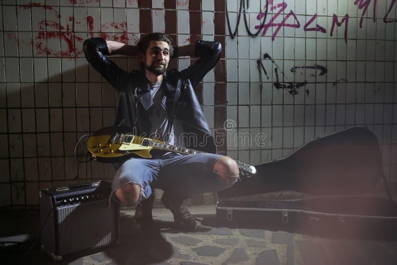 坐和拿着在地下过道的街道音乐家一把吉他 无业游民的生活方式 在地下过道谋生的使用 库存图片