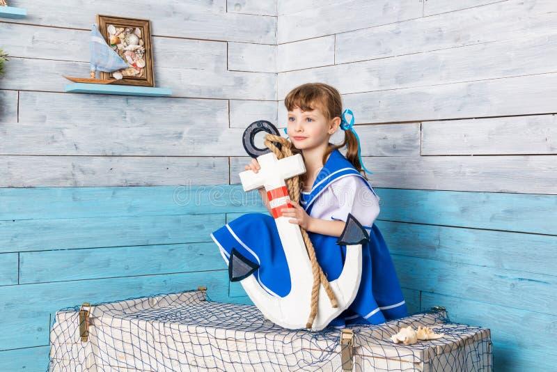 坐和拿着船锚的小女孩 免版税库存图片
