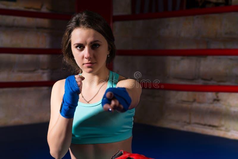 坐和握紧她的拳头的年轻女性拳击手 库存照片