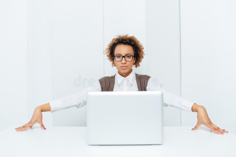 坐和摆在与膝上型计算机的严肃的非裔美国人的女实业家 免版税库存照片