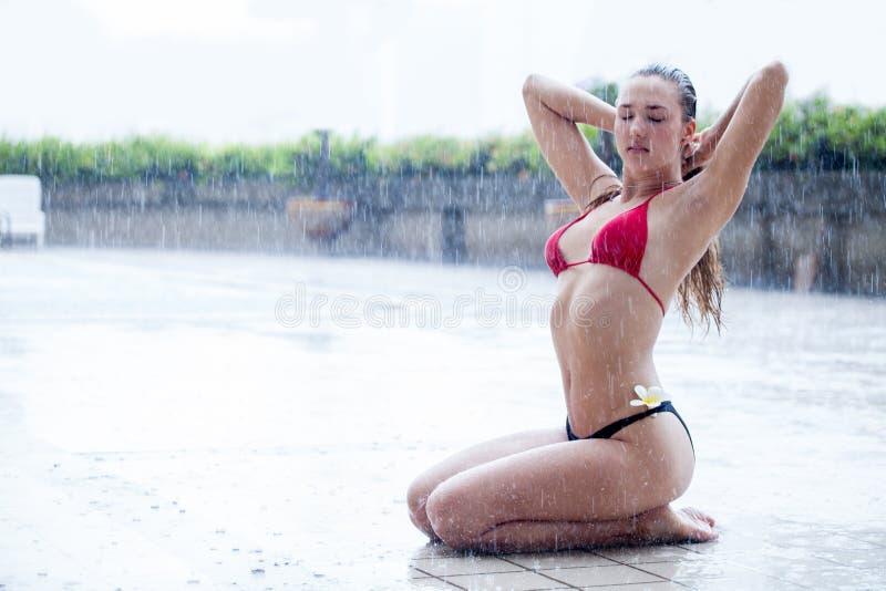 坐和摆在由游泳场的比基尼泳装的美丽的年轻女人户外在雨季节 泳装休息的性感的女性 免版税库存照片